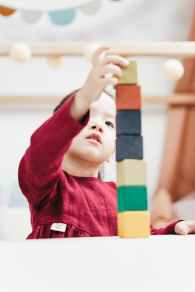selective focus photo of young girl in red dress playing with building blocks