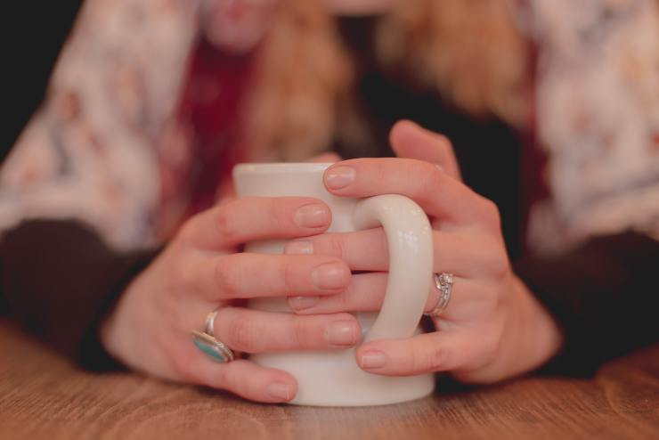 This is a picture of a woman holding a cup of coffee. It represents someone taking time.  Just like the nurses at Nurtured Well, LLC will take time to listen to you.