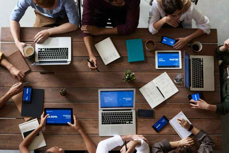 top view photo of people near wooden table on computers. They are looking for great women's health tips for you.