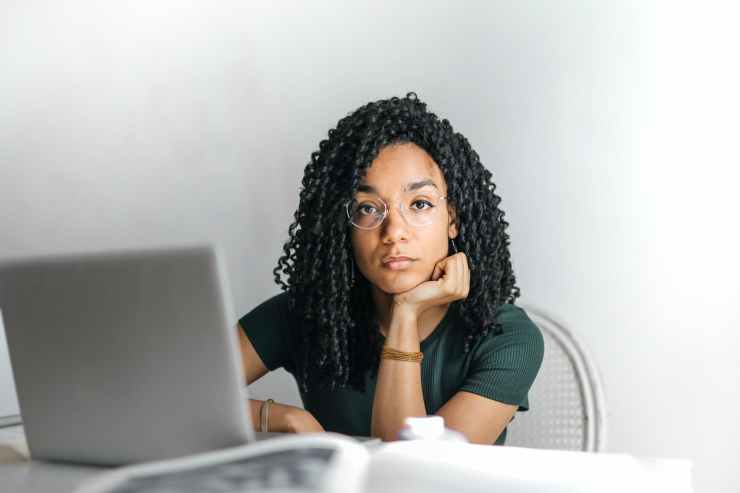 serious ethnic young woman using laptop at home.  She is emailing Nurtured Well, LLC  to get help with her bipolar disorder.