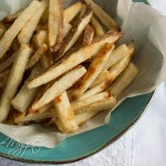Crispy Baked French Fries on parchment paper on rustic teal bowl