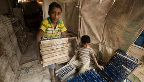 Bocah Bangladesh tampak sedang bekerja mengangkat barang. Foto Via DW