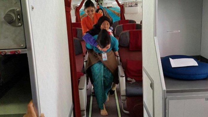 vera sang pramugari saat gendong nenek turun dari pesawat. foto ist