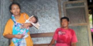 Balita Mardiyah dalam gendongan sang ibu. Foto Tri Wahyudi/ NusantaraNews.co