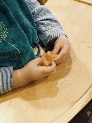 Enfant épluche une mandarine