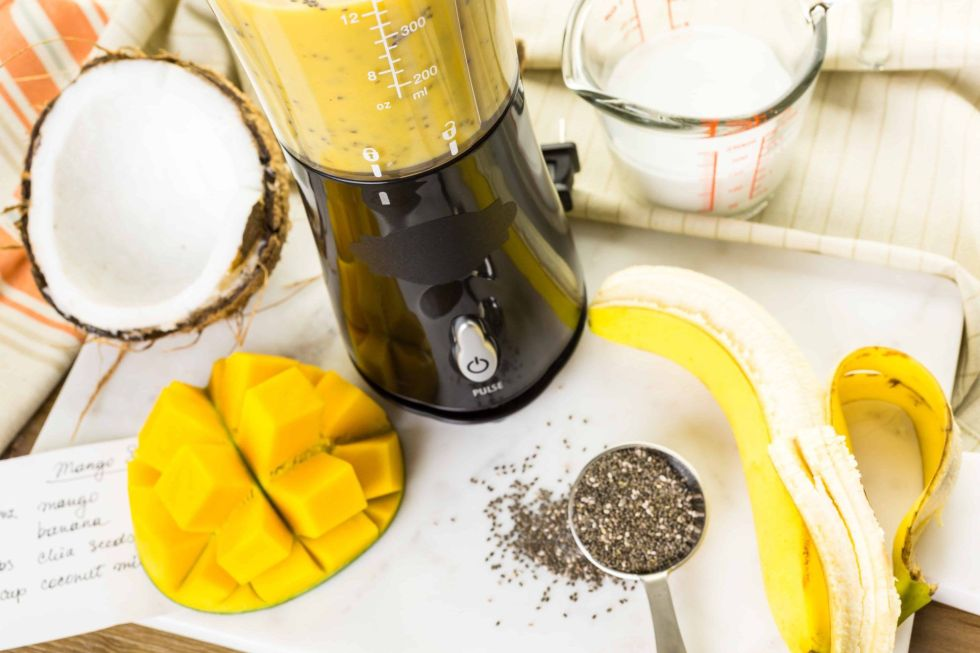 Portable blender making mango banana smoothie with chia seeds.