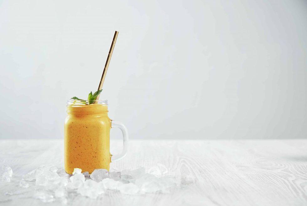 Mango smoothie surrounded by ice