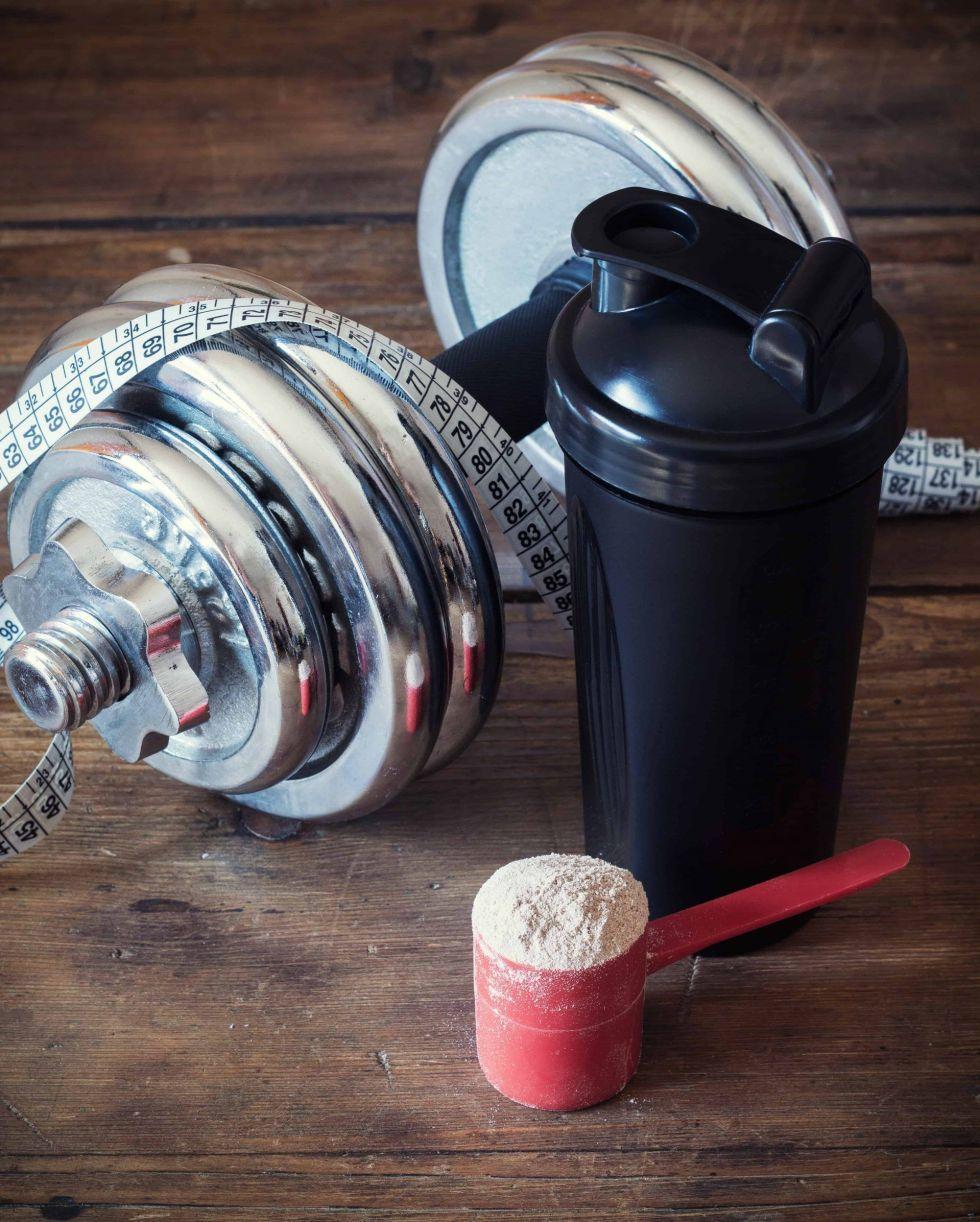 Protein powder next to a protein blender