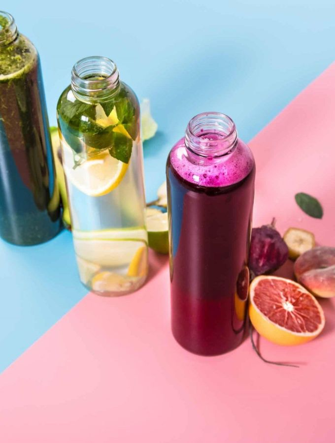 Glass juicing bottles with natural detox drinks and a variety of fruits and vegetables on a pink and blue background .