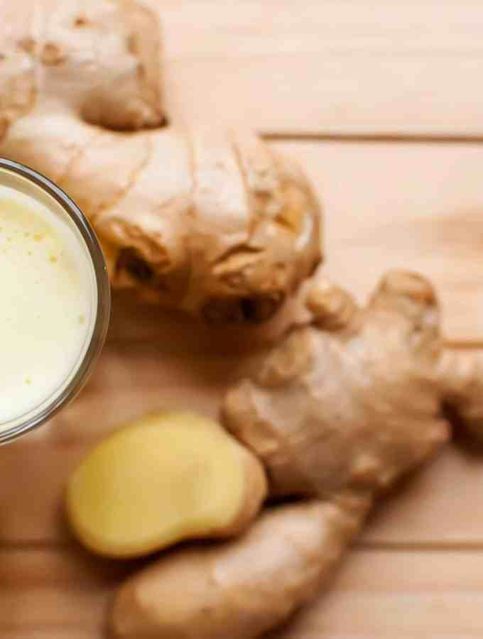 Ginger juice shot next to pieces of ginger on a wooden table