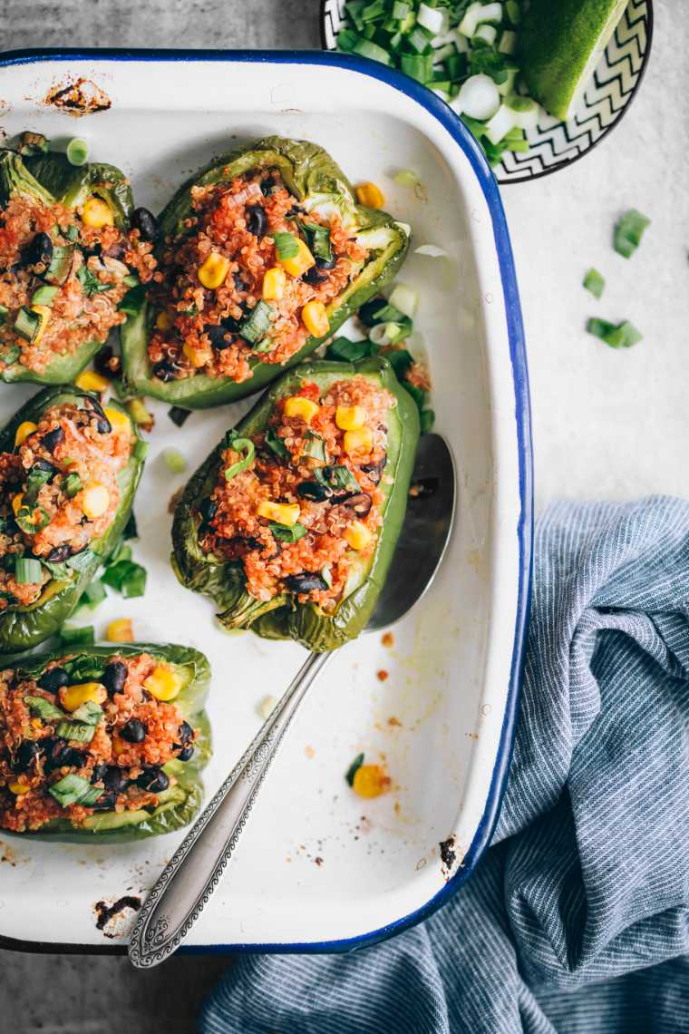 white baking dish on a table with five green plant-based stuffed peppers