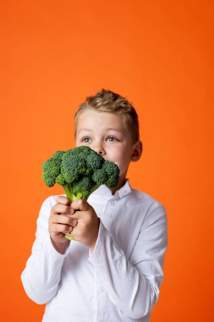 This shows a fussy eater holding some broccoli