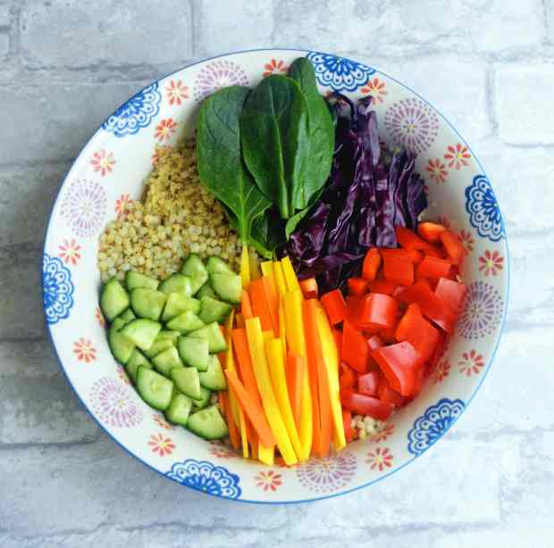 A vegan & gluten-free grain bowl topped with rainbow veggies