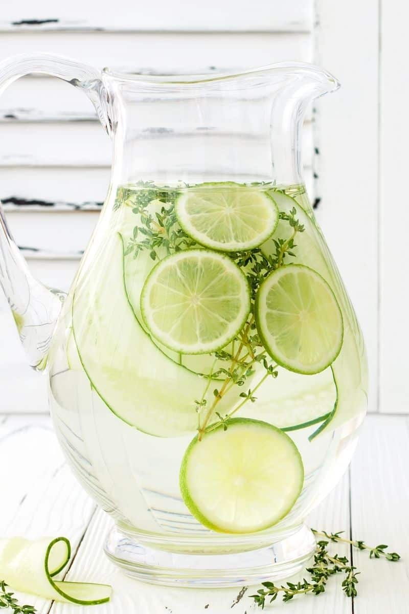 glass pitcher with water and cucumber and limes