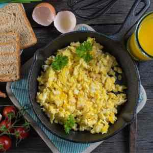 skillet with scrambled eggs next to toast and glass of orange juice