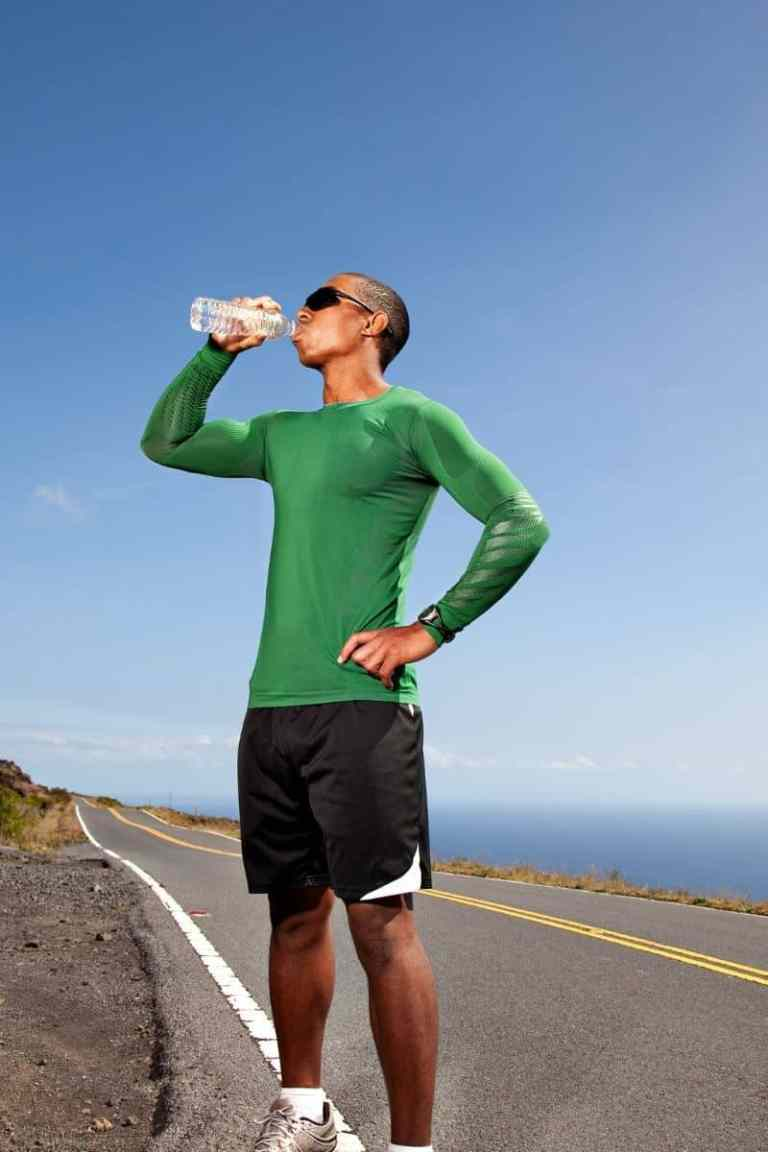 man in green shirt drinking water on side of road
