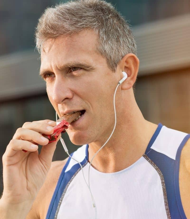 man eating bar with headphones before a run