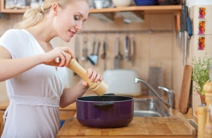 Girl cooking with pepper grinder