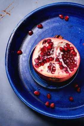 Half pomegranate on a blue plate