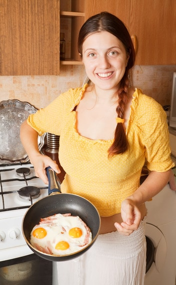 Young woman with fried eggs and bacon