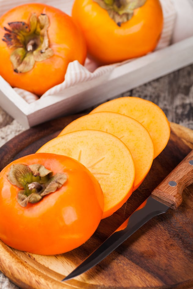 Sliced persimmons on a board
