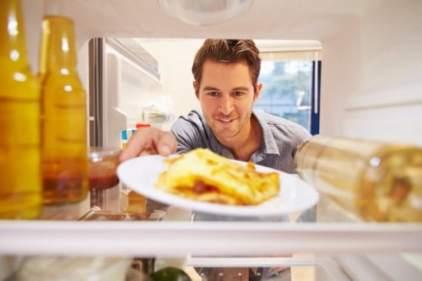 Man Looking Inside Fridge Full Of Unhealthy Food