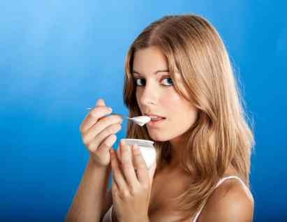 Woman eating yogurt looking surprised