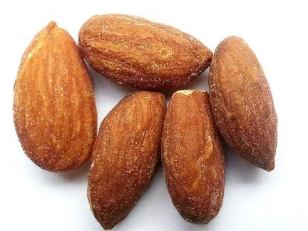 Five almonds, white background