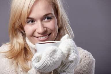 Warm girl drinking cocoa or coffee