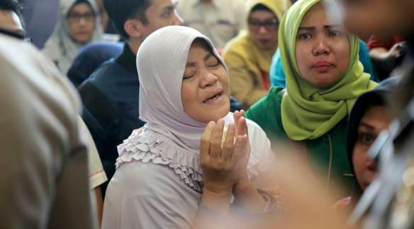 A relative of passengers prays as she and others wait for news on a Lion Air plane that crashed off Java Island at Depati Amir Airport in Pangkal Pinang, Indonesia Monday, Oct. 29, 2018. Indonesia disaster agency says that the Lion Air Boeing 737-800 plane crashed into sea shortly after it left Indonesia's capital Monday morning. (AP Photo/Hadi Sutrisno)