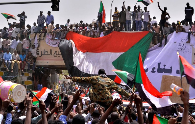 "A military officer is carried by the crowd as demonstrators chant slogans and carry their national flags, after Sudan's Defense Minister Awad Mohamed Ahmed Ibn Auf said that President Omar al-Bashir had been detained ""in a safe place"" and that a military council would run the country for a two-year transitional period, outside Defence Ministry in Khartoum, Sudan April 11, 2019. REUTERS/Stringer TPX IMAGES OF THE DAY - RC158D03E8D0"