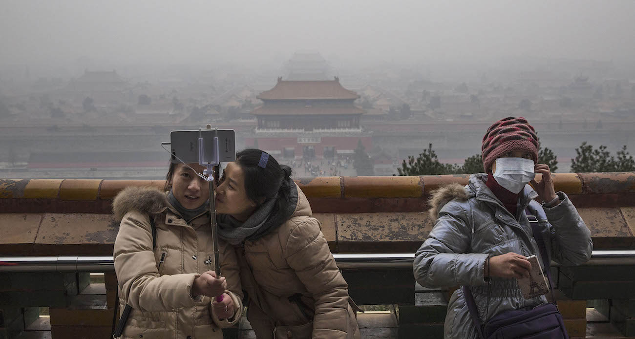 """BEIJING, CHINA - DECEMBER 08:  A Chinese woman wears a mask to protect against pollution as two women take a picture together while visiting Jingshan Park overlooking the Forbidden City in heavy smog on December 8, 2015 in Beijing, China. The Beijing government issued a """"red alert"""" for the first time since new standards were introduced earlier this year as the city and many parts of northern China were shrouded in heavy pollution. Levels of PM 2.5, considered the most hazardous, crossed 400 units in Beijing, lower than last week, but still nearly 20 times the acceptable standard set by the World Health Organization. The governments of more than 190 countries are meeting in Paris to set targets on reducing carbon emissions in an attempt to forge a new global agreement on climate change.  (Photo by Kevin Frayer/Getty Images)"""