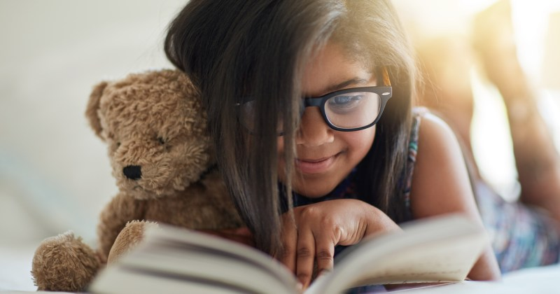 Girl in glasses reading a book