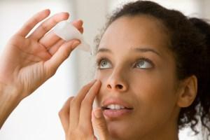 Woman putting eye drops