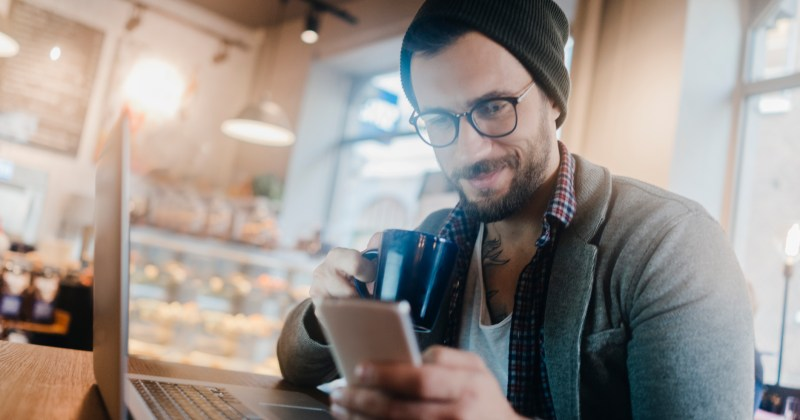 Man using a smart phone in cafe