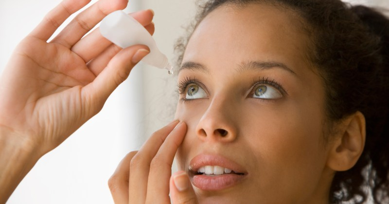 Young woman putting eye drops