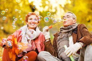 Cheerful senior couple blowing bubbles in park