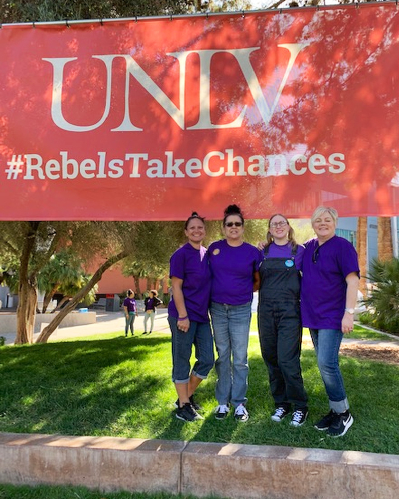 Four people under a UNLV banner