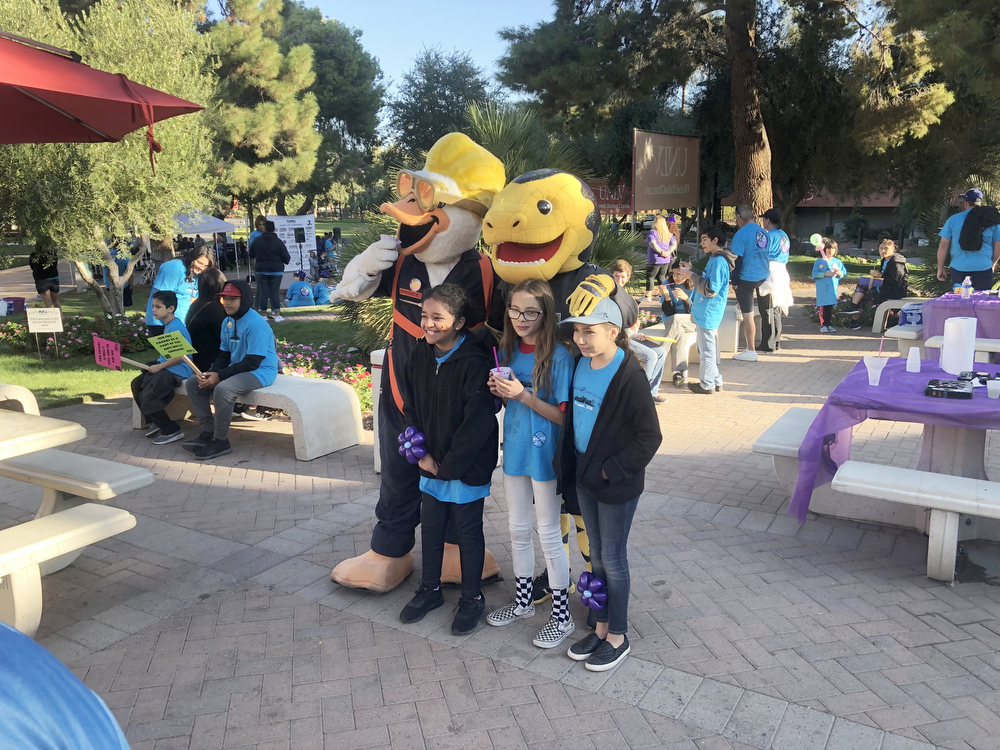 Three children for a photo with the mascots from the Las Vegas Aviators, and Golden Knights