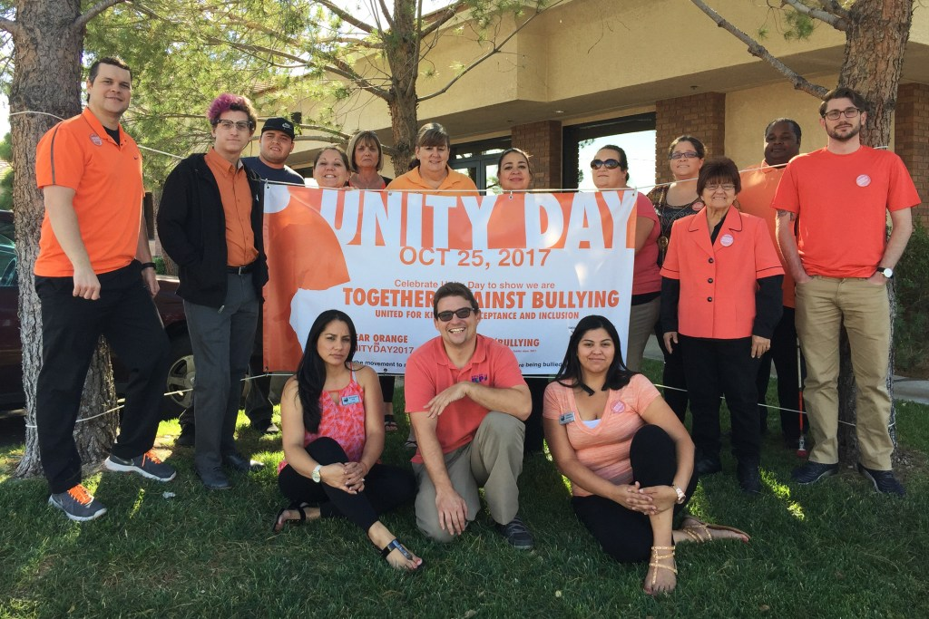 Pep Staff photo in front of a Unity Day banner