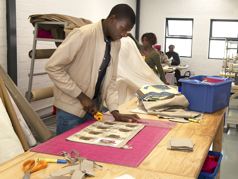 WhimsicalCollection on Nwabisa African Art, Man cutting fabric in factory