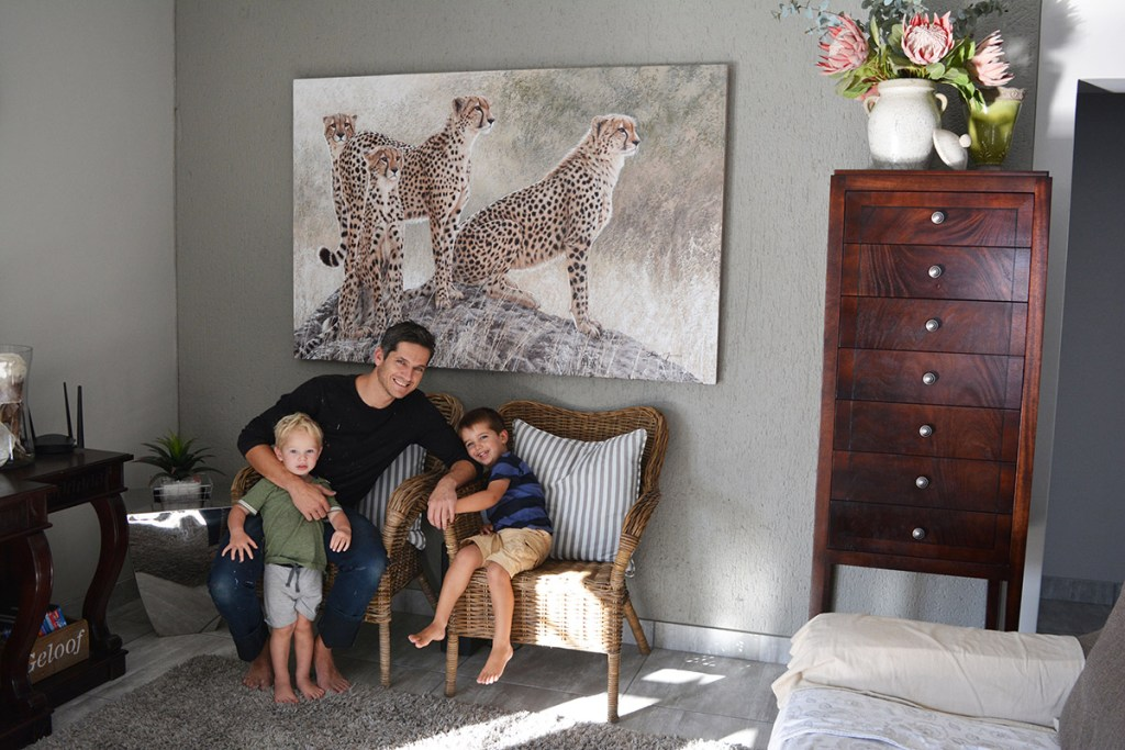 Danie Marais with his children and the painting Hunting g for hope