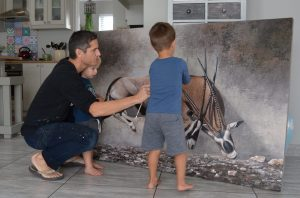 Danie Marais with his sons Karlo and Luka and the painting Clashing of horns