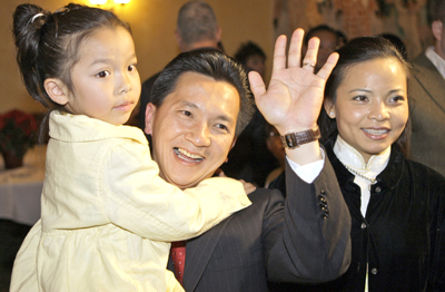 Republican Anh 'Joseph' Cao waves as he holds his daughter Betsy Cao, 4, with his wife Kate Hieu Hoang, right, at his victory party after defeating Rep. William Jefferson, D-La., for the 2nd Congressional District in New Orleans Saturday, Dec. 6. (Photo provided by the Associated Press.)