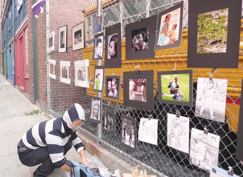 Artist Ben Zheng hangs up his artwork at the neighborhood art walk organized by SCIDpda. (Artist Ben Zheng hangs up his artwork at the neighborhood art walk organized by SCIDpda.)