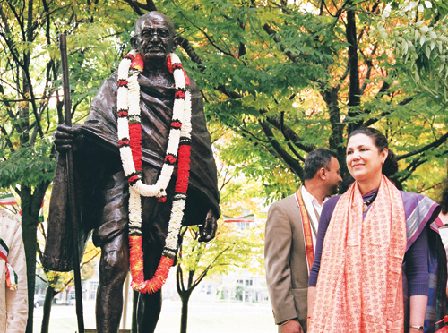 Ambassador of India to the United States Meera Shankar stands next to the new bronze statue of Mahatma Gandhi at Bellevue Public Library during its unveiling on Oct. 17. (Photo by James Tabafunda/NWAW)