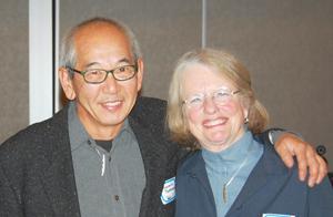 "Mimi Gardner Gates stands with Gerald ""Gerry"" Tsutakawa, an accomplished sculptor. Gates and Tsutakawa are wearing necklaces made by Tsutakawa. (Photos by George Liu/NWAW)"