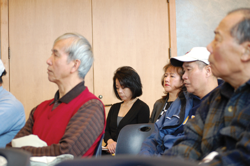 """Doris Wong-Estridge (middle, wearing black) and her sister Carrie Wong, nieces of Wah Mee Massacre victim Wing """"Bill"""" Wong, sit indiscreetly at a public meeting with the Indeterminate Sentencing Review Board on Dec. 4 at Beacon Hill Library. The meeting was designed to gain public input on whether Wah Mee inmate Tony Ng should be granted parole. (Photo by George Liu/NWAW)"""