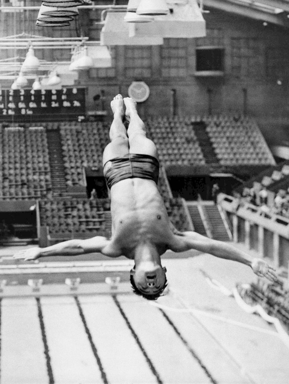 In this July 27, 1948, file photo, Sammy Lee, member of the U.S. Olympic diving team, dives from the top of the diving tower during training at the London Olympics at the Empire Pool in Wembley, England.  (AP Photo/Laurence Harris)