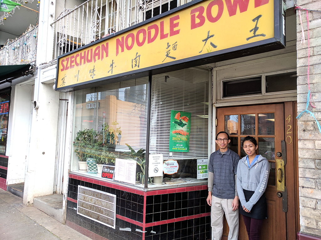 YingQui and Kelly Huang stand beside the food rating they received at the entrance of their restaurant. (Photo by Janice Nesamani/NWAW)